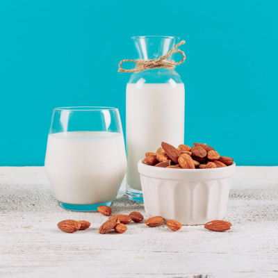 Bottle of milk with glass of milk and bowl of almonds side view